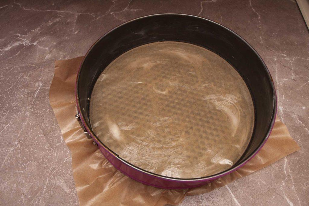 застилаю дно формы для пирога с апельсинами в духовке пергаментом и смазываю ее сливочным маслом