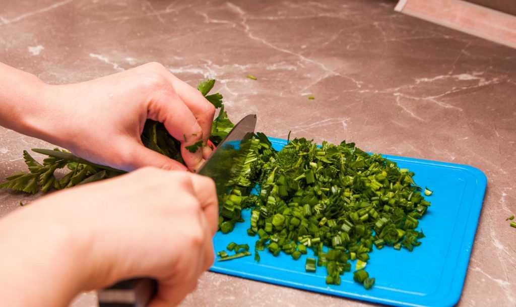 Шинкую зелень. Яичный суп с помидорами должен быть насыщен зеленью