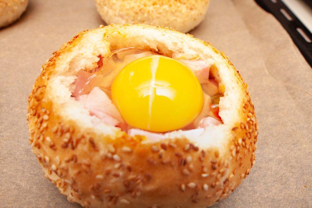 Перед началом запекания в духовке в булочки добавляем желток яйца