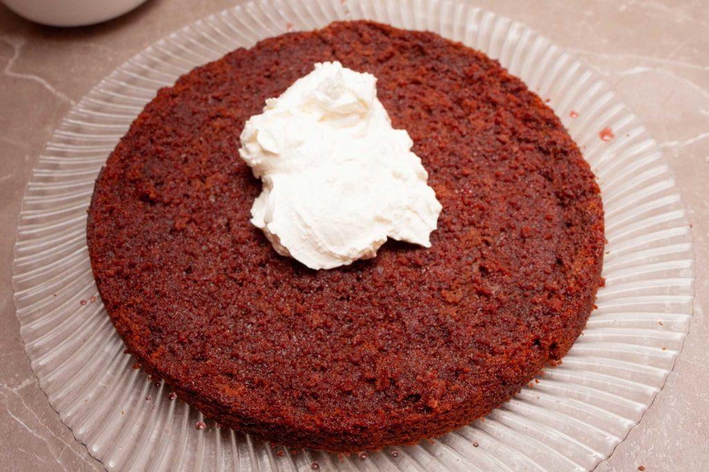Распределяем творожный крем на корж шоколадного торта.
