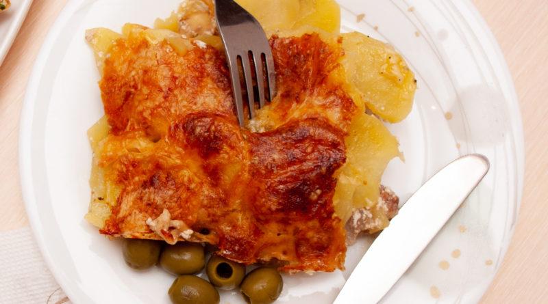 Картофель по-французски в духовке с говядиной и сыром на тарелке