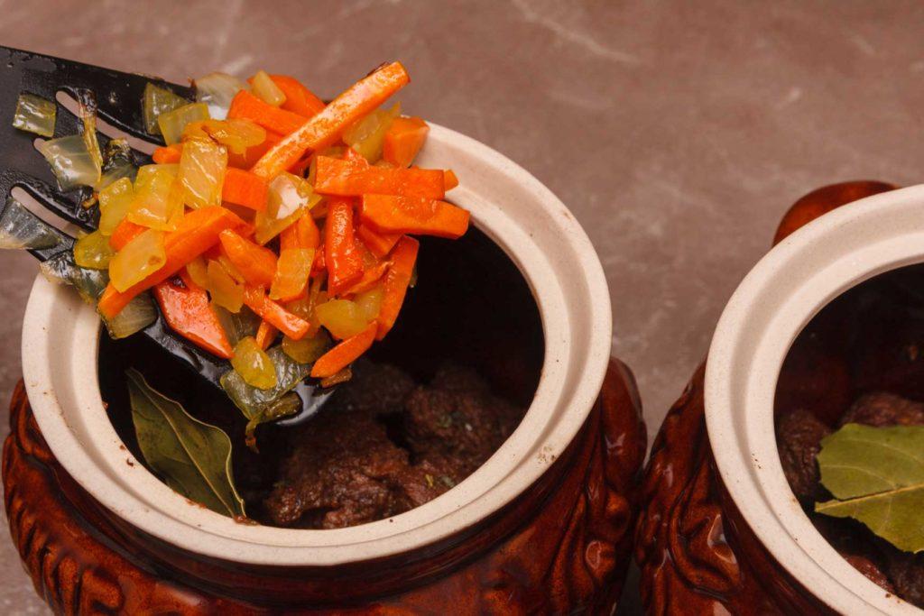 добавляю пассеровку из лука и морковки в горшочки