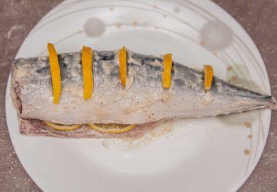 достаю скумбрию из холодильника и вставляю в поперечные разрезы ломтики лимона, пару кусочков кладу в середину рыбы