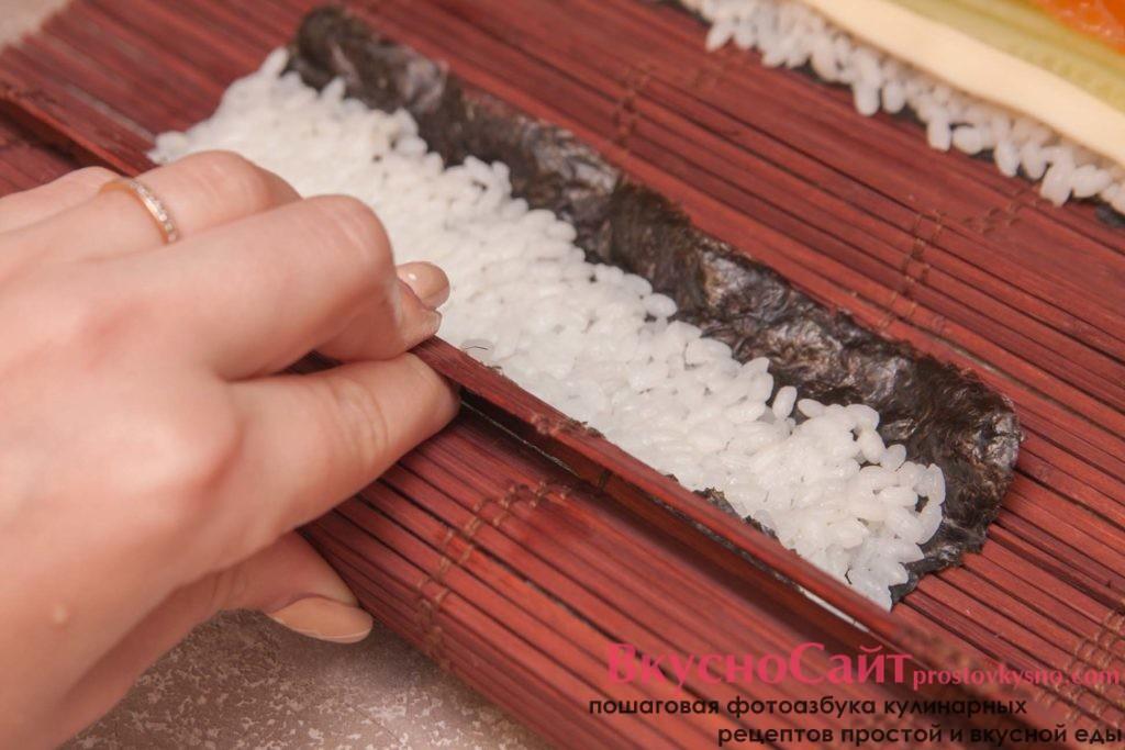 поочередно сворачиваю рулеты из нори при помощи бамбукового коврика
