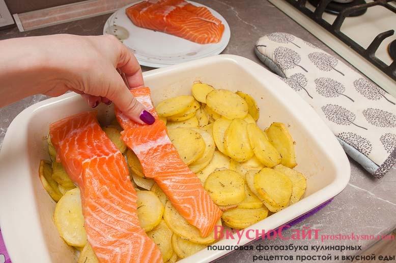 достаю картофель из духовки и сверху на картошку выкладываю рыбу, рыбу немного солю