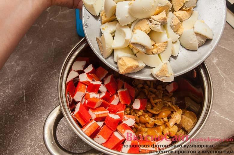 в кастрюлю с грибами отправляю нарезанные крабовые палочки и яйца