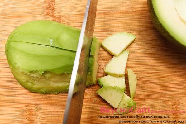 Авокадо разрезаю напополам, извлекаю косточку, чищу от шкурки и нарезаю тонкими четвертинками. Кладу сверху на салат.