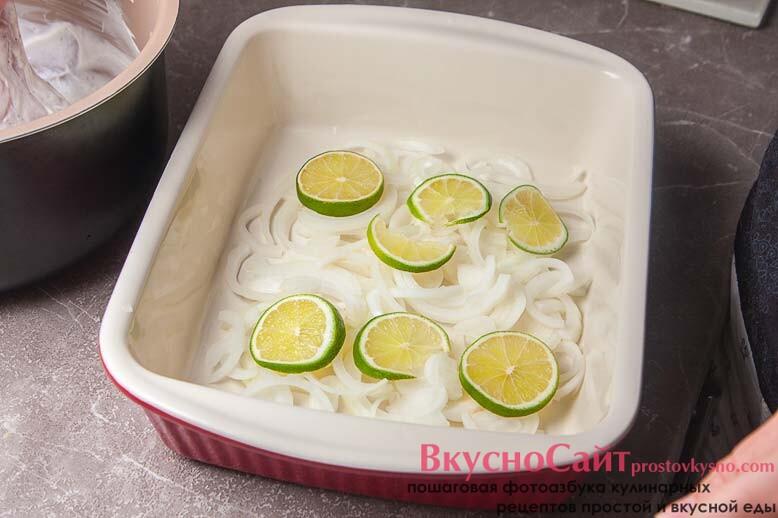на лук выкладываю дольки лайма, сбрызгиваю все оливковым маслом и посыпаю щепоткой соли и перца