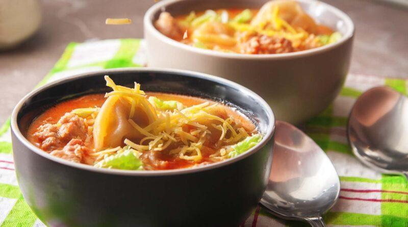 Суп с пельменями и купатами в тарелке
