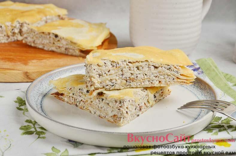 Блинный торт с курицей и грибами на тарелке