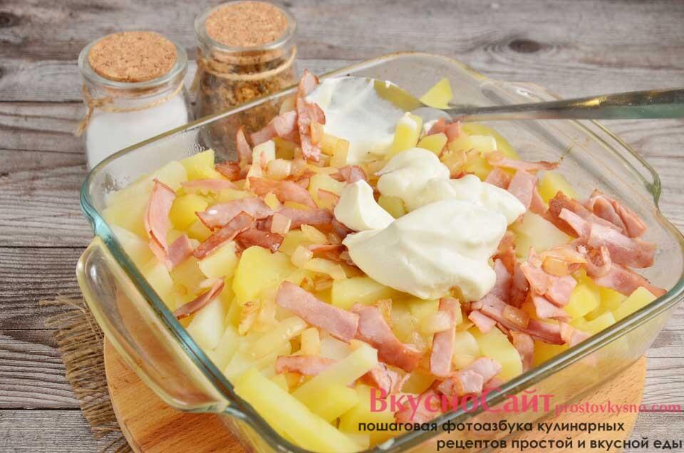отправляю картофель в форму, смазанную маслом, добавляю зажарку, соль и сметану, все перемешиваю