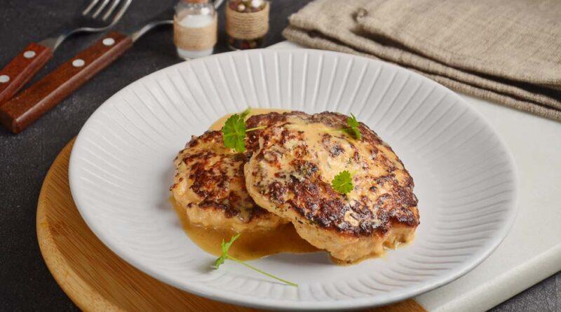 Куриные котлеты в сметане на сковороде лежат на тарелке