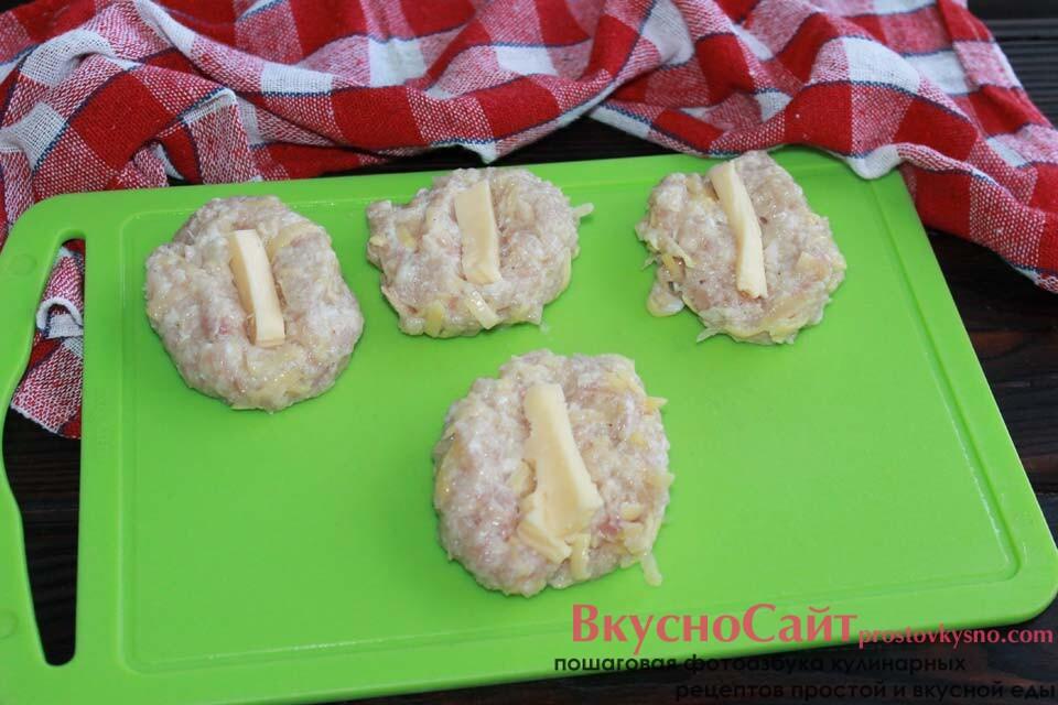 из фарша формирую лепешки, помещаю их на разделочную доску, в центр каждой кладу сырный брусок